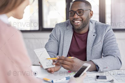 African male in formal clothes discusses details of new project to his assistant, explains charts an