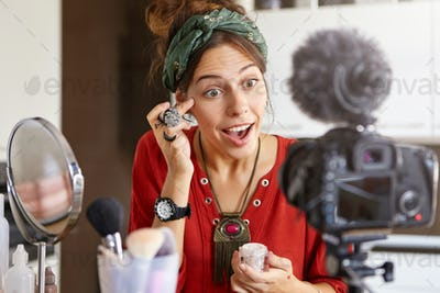 Young female using cosmetic product for her blog, recording tutorial video. Pretty fashionable femal
