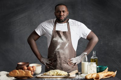 Confident serious dark skinned male chef wears apron, keeps hands on waist as stands near table with