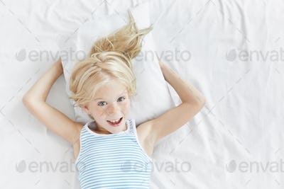 Indoor portrait of emotional blue eyed lovely female child with blonde hair and freckled face having