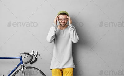 Sickness, migraine, unwellness and health problems. Picture of stylish unshaven Caucasian guy wearin