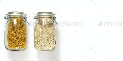 Stocks of non-perishable products in glass jars on a light background.