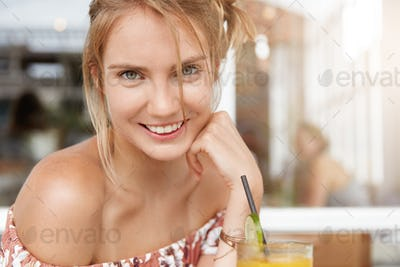 Close up shot of pleasant looking female model with shining broad smile, being in good mood, spends