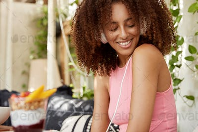Sideways shot of pleasant looking female with Afro hairstyle, listens audio track in headphones, loo