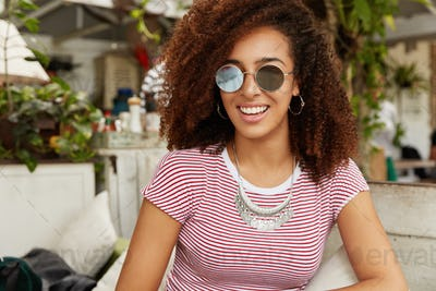 Shot of pleasant looking young African American female model with curly bushy dark hair, wears styli