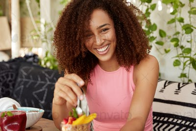 Curly woman with cheerful expression, eats delicious dessert, being in good mood, spends spare time