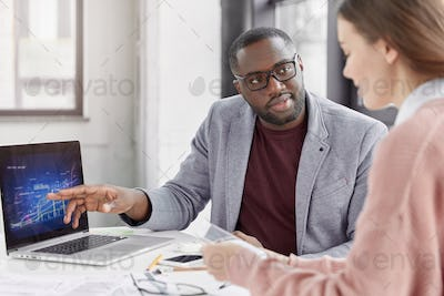 Serious black African American male tries to explain his female trainee startegy of development sale