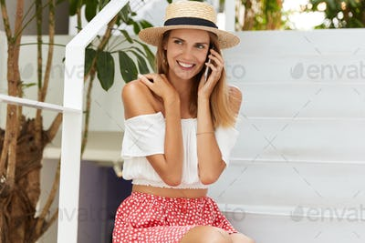 Happy female model poses on white stairs, wears stylish summer hat, blouse and skirt, has pleasant p