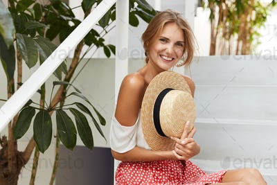 Glad young female model has postive smile holds staw summer hat and dressed in fashionable clothes,