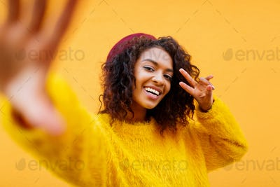 Attractive  African woman with wavy hairs  making self portrait