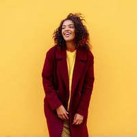 Black girl in winter outfit and accessories posing on yellow background.