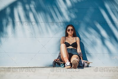 Nude asian girl poses around wall in daytime with her skateboard