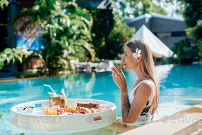 Beautiful female traveller drinks cocktails in swimming pool in hotel