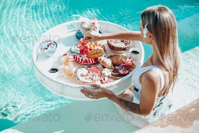 Slim woman with tattooed hand swims in pool eating asian food