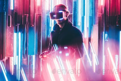 man using joystick in hands and VR headset on head playing in neon light