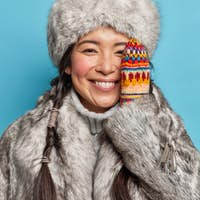 Close up shot of happy shy arctic woman keeps hands on cheek wears warm gloves fur coat and hat spen