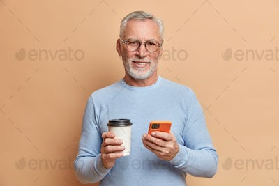 Indoor shot of handsome bearded mature man has free time after work checks social networks on smartp