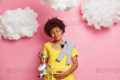 Ethnic pregnant woman holds tummy and has contractions going to give birth holds baby mobile toy and