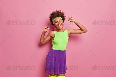 Studio shot of energized positive Afro American woman dances with joy keeps hands raised enjoys holi
