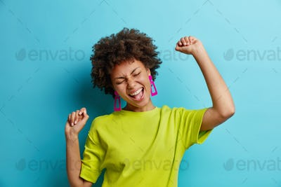 Overjoyed African American woman makes winning gesture expresses happiness raises arms and dances ca