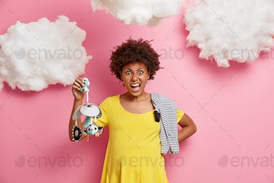 Angry future mother holds mobile toy shouts irritated dressed in yellow dress has big abdomen carrie