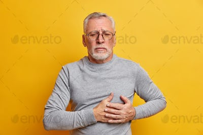 Displeased senior man presses hand to chest has heart attack needs pinkillers dressed in casual turt