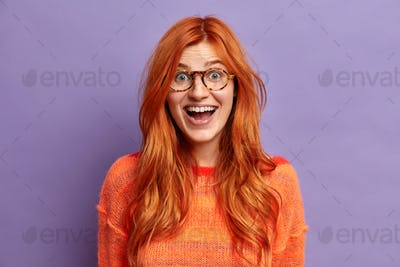 Headshot of excited ginger European woman looks with glad face expression cannot believe her success