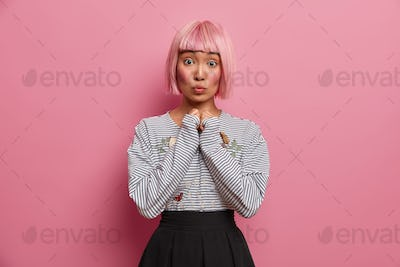 Cute Asian teenage girl with surprised face expression keeps lips rounded hands together shocked to