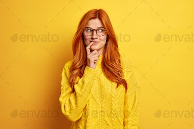 Portrait of pleased nice looking young woman keeps index finger near lips concentrated aside has tho