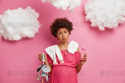 Exhausted tired pregnant woman with tummy holds milk bottle toy mobile carries diaper and bodysuit o