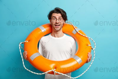 Positive surprised man poses with inflated lifebuoy wears round spectacles and white t shirt eager t