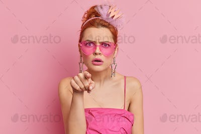 Angry redhead young woman wears stylish sunglasses and dress indicates directly at camera with annoy