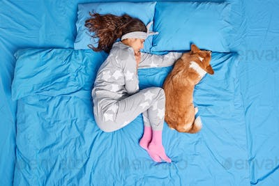 Top view of brunette young European woman in pajama sleeps together with favorite pet sees sweet dre