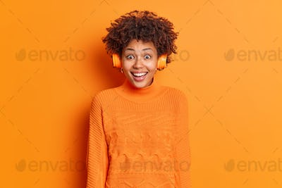 Happy reaction concept. Overjoyed curly haired African American woman wears stereo headphones enjoys