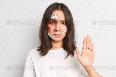 Horizontal shot of ypung Asian woman makes stop gesture and asks to stop hurting her becomes victim