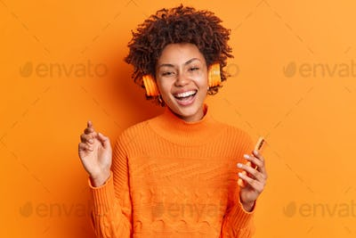 People entertainment and hobby concept. Cheerful young African American woman with curly hair holds
