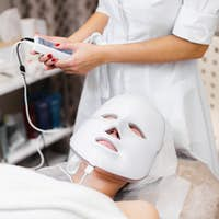 The client lies in the salon on the cosmetology table with a white mask on her face