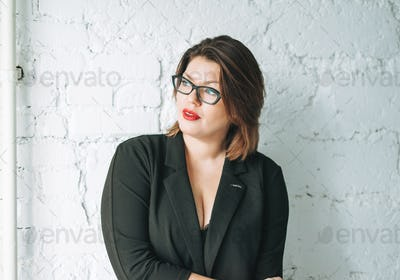Young woman business lady in glasses and black jacket against white wall