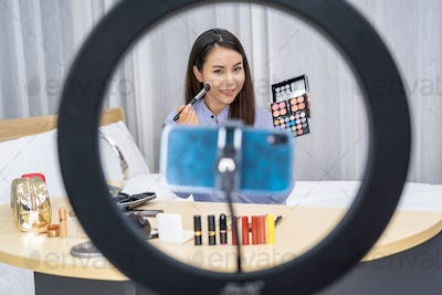Glamour Asian woman beauty blogger or vlogger showing make up with palette and Live