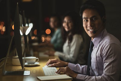 Portrait of Asian Male customer care service with businesswoman smiling and working hard