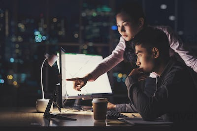 Asian businesswoman and businessman working hard late together with technology computer