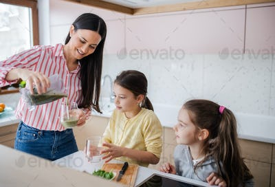 Mother with girls indoors at home, preparing fruit smoothie drink.