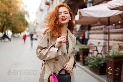 Romantic woman with red hairs and bright make up walking on the street.