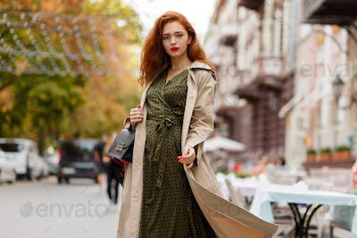 Beautiful  woman with red hairs and bright make up walking on the street.