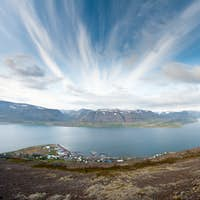 fjord surrounded by mountains bathing in evening light