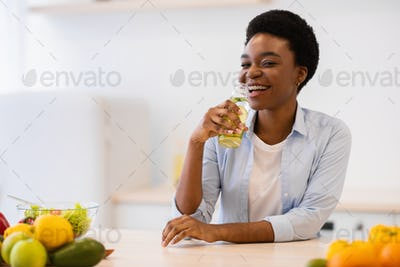 Black Lady Drinking Infused Water For Refreshment In Modern Kitchen
