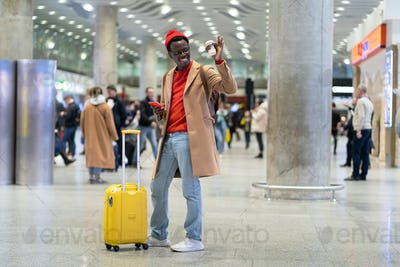 Afro-American man stands in airport after arrival, holding mobile phone, cup coffee, say hello