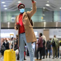 African American millennial man in face mask stands in airport terminal, using phone, raising hand