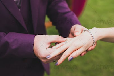Groom wearing ring on bride's hand on wedding ceremony close-up