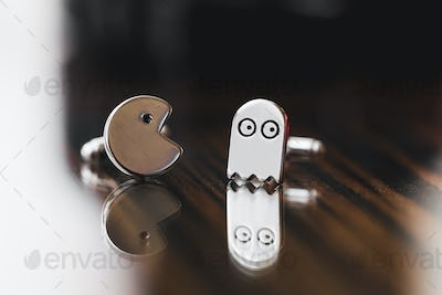Cufflinks in Pacman shape close-up on wooden texture. Funny style pac man